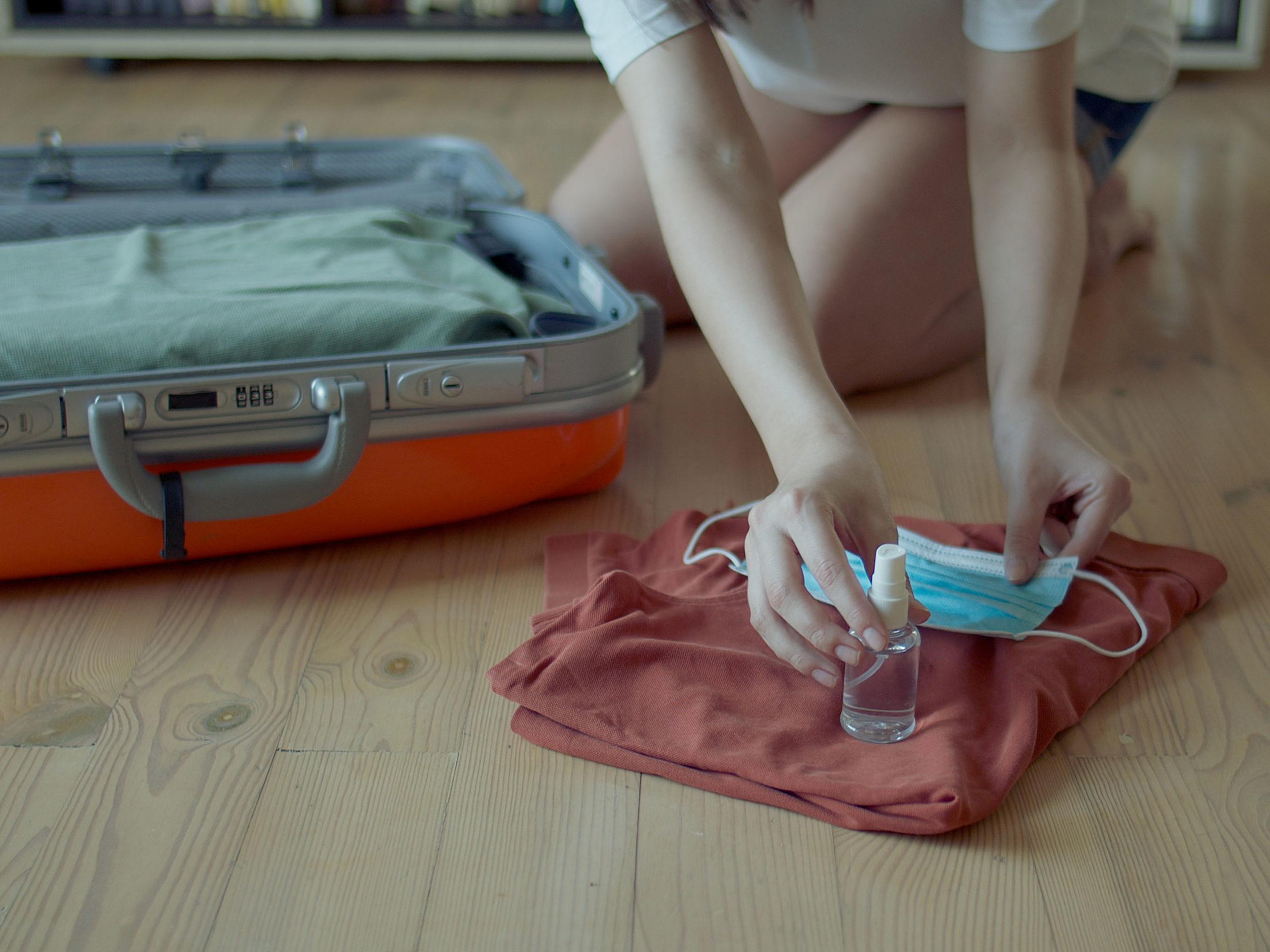 Woman packing mask and sanitizer